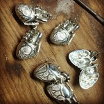 Polished silver heart lockets in progress.